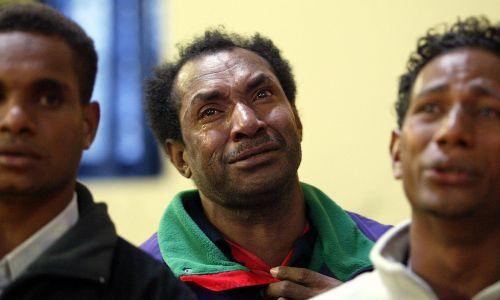 Ubiegający się o azyl uciekinierzy z Zachodniej Papui podczas porannej mszy świętej w kościele anglikańskim w St. Andrews w Somerville w stanie Massachusetts. Jeden z mężczyzn płacze, śpiewając hymn. To Yunus Wainggai, który uciekł wraz z 4-letnią córką Anike, pozostawiając swoją żonę Siti Pandera Wainggai – teraz boi się o jej bezpieczeństwo. Stany Zjednoczone, kwiecień 2006 r. Fot.  AGE NEWS, Pat Scala/Fairfax Media via Getty Images