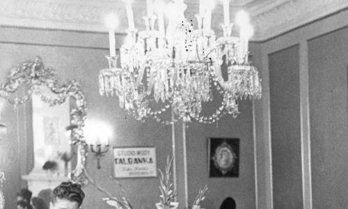 """""""Falbanka"""" nie była zamkniętą instytucją niemiecką, na fotografii widać jej polską nazwę. Była przedstawiana jako studio mody dla wszystkich, bo jego personel rozumie trudne warunki życia i zawsze pomoże w przerobieniu jakiejś starej sukienki w modny sposób. Tu: klientki salonu mody w rozmowie z ekspedientką. Fot. NAC/Jerzy Łuczyński, Wydawnictwo Prasowe Kraków-Warszawa, sygnatura: 2-7141"""