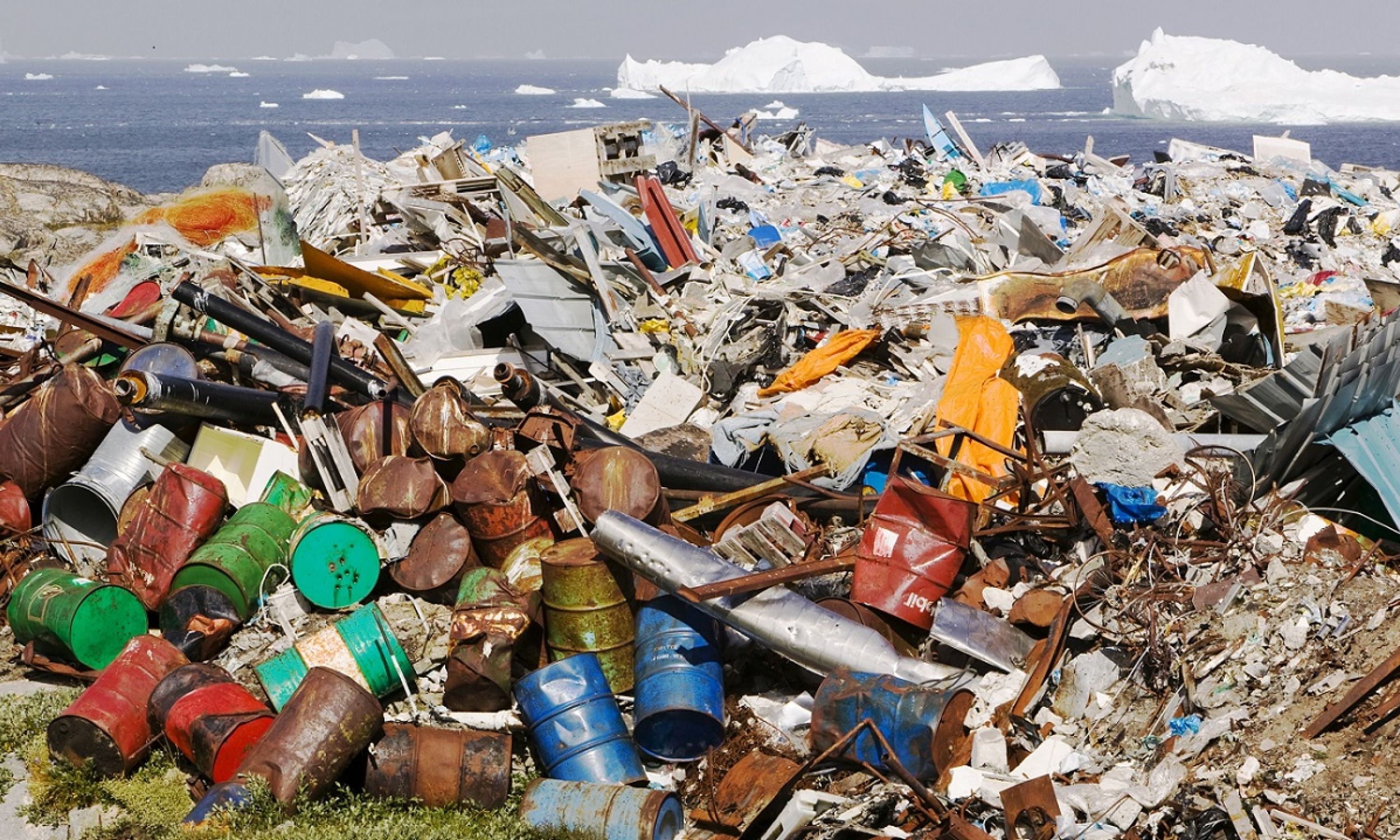 Beczki po ropie wyrzucone w okolicy miasta Ilulissat w Grenlandii, w tle góry lodowe Icefjord w lipcu 2008. Zdjęcie Ashleya Coopera, którego potem aresztowano w Chinach za fotografowanie niszczycielskich skutków zmian klimatu. 54-latek obrazował książkę, opisującą efekty globalnego ocieplenia od Alaski, gdzie rozpoczął podróż, do Boliwii, gdzie skończył. 14 lat wcześniej był świadkiem, jak z powodu tych zmian domy utraciło 600 mieszkańców Alaski. Fot. Ashley Cooper/Barcroft Media via Getty Images