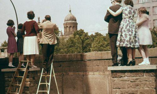 Ludzie z Kreuzberg niedaleko Heinrich-Heine-Strasse patrzą na mur berliński w kierunku wschodniego Berlina, za kościołem św. Michała we wschodniej części miasta. Początek lat 60. Fot. Leber / ullstein bild via Getty Images