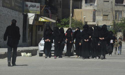 Uczennice niejscowej szkoły na ulicach miasta zajętego przez ISIS.  Fot. REUTERS/Stringer