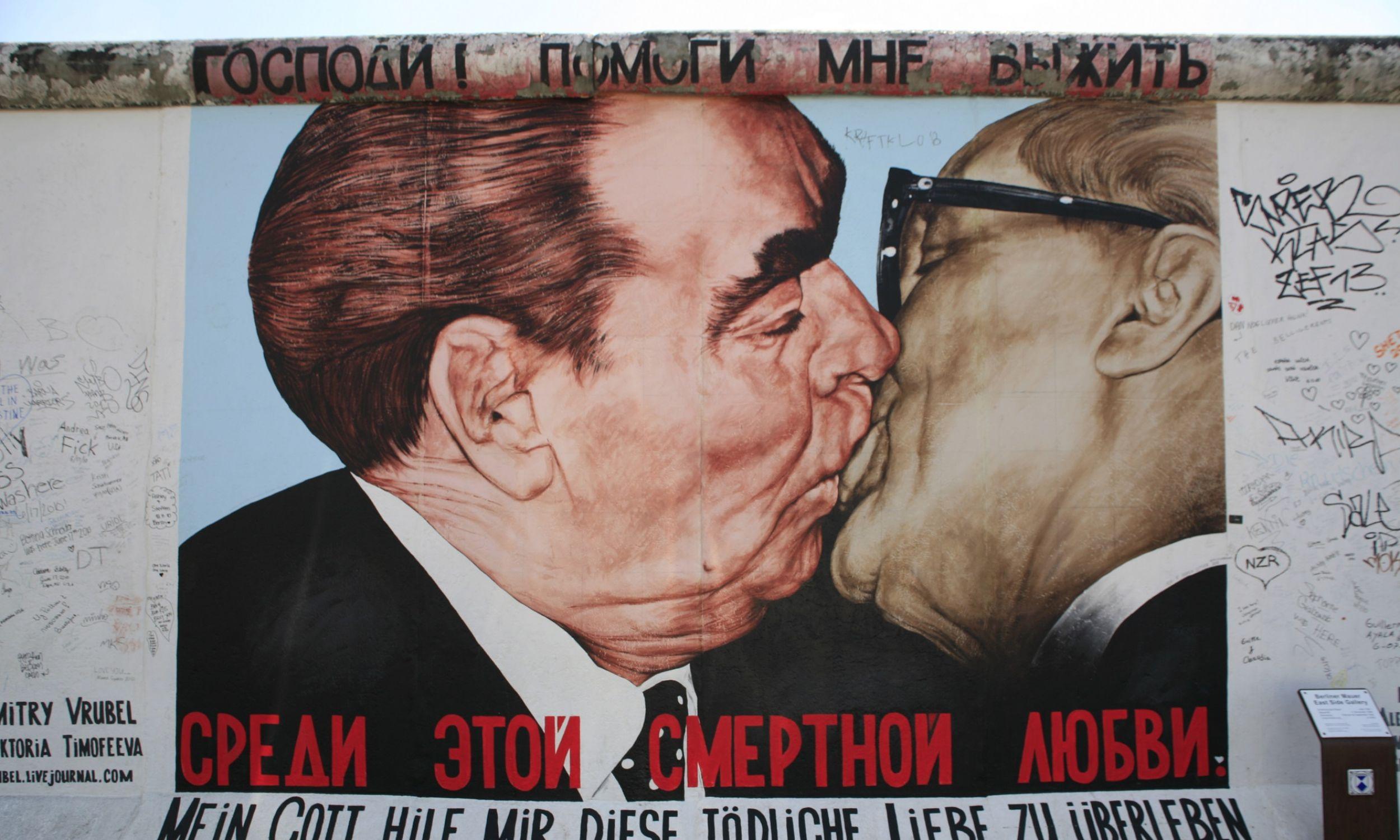 """Galeria East Side – mural  """"Bruderkuss"""" artysty Dimitry'ego Vrubla  na Murze Berlińskim, najdłuższym pomniku pokoju i pojednania w Berlinie. Fot. Raimund Franken / ullstein zdjęcie via Getty Images"""