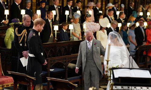 Książę Harry patrzy na swoją narzeczoną Meghan Markle, którą prowadzi do ołtarza książę Walii Karol.  Fot. REUTERS /Jonathan Brady