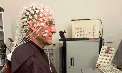 Aby połączyć ze sobą mózgi, trzeba skojarzyć jakąś metodę obrazowania mózgu – w omawianym wypadku elektroencefalografię (EEG) – z jakimś sposobem na neurostymulację. Na zdjęciu Barry Kerzin podczas EEG wykonywanego w badaniach neuronauki (interdyscyplina zajmująca się układem nerwowym; leży na pograniczu wiedzy medycznej, biologicznej, biochemicznej, biofizycznej, informatycznej, psychologicznej). Fot. Antoine Lutz - Barry Kerzin, Domena publiczna, https://commons.wikimedia.org/w/index.php?curid=43330167