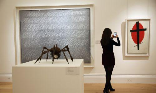 """Pracownica londyńskiego domu aukcyjnego Sotheby's robi zdjęcie dzieła """"Mistyczny suprematyzm (Black Cross Red Oval)"""" Kazimierza Malewicza, 9 października 2015 r. Obraz w listopadzie wystawiono na licytację w Nowym Jorku i sprzedano za 37,7 miliona dolarów amerykańskich. Fot. Dan Kitwood / Getty Images"""