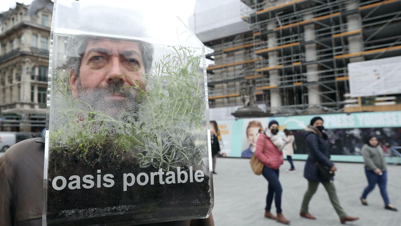 """Po ulicach Brukseli artysta przechadza się z """"przenośną oazą"""" (fot. YVES HERMAN/Reuters/Forum)"""