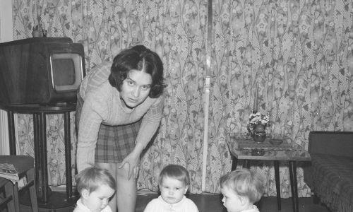 """Kobieta z trojaczkami, w tle widoczny telewizor """"Wisła"""". Zdjęcie wykonane między 1967 a 1970 rokiem. Fot. NAC/Grażyna Rutowska, sygn. 40-D-22-4"""