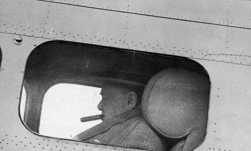Brytyjski przywódca Winston Churchill (1874 - 1965) pali cygaro w samolocie startującym z lotniska Biggin Hill w Kent, 23 lipca 1949. Fot. Keystone / Hulton Archive / Getty Images