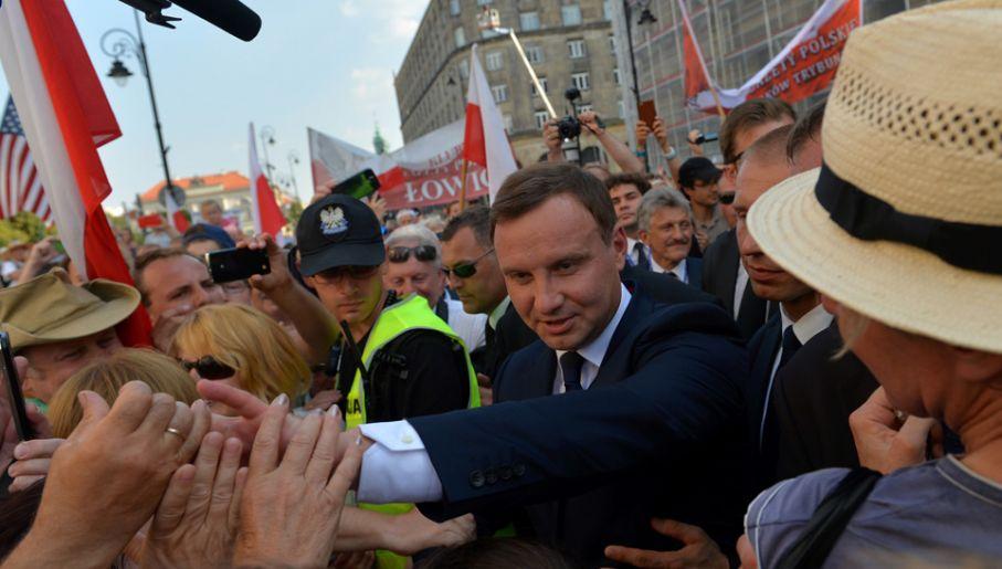 Prezydent Andrzej Duda rozmawia i wita się z osobami tłumnie zgromadzonymi na trasie jego przejścia z pl. Piłsudskiego do Pałacu Prezydenckiego (fot. PAP/Marcin Obara)