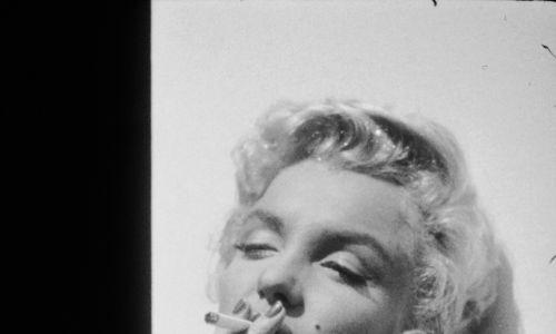 """Paliły wsystkie światowe seksbomby. Amerykańskiego aktorka Marilyn Monroe (1926-1962, tu opiera się o drzwi przyczepy w studiu 20th Century Fox podczas zdjęć do filmu z 1954 r. """"Nie ma takiego biznesu jak show biznes"""" reżysera Waltera Langa)... Fot. Gene Lester / Getty Images"""