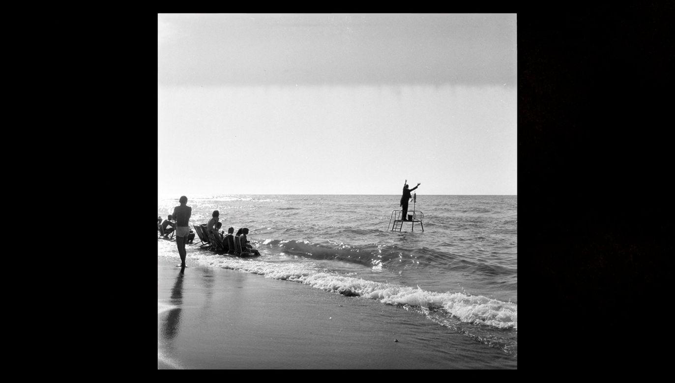 """Słynne jest zdjęcia Eustachego Kossakowskiego, jak Edward Krasiński dyryguje falami Bałtyku, stojąc na brzegu. Potem to zdjęcie było powtarzane w wielkim formacie na wszystkich stacjach paryskiego metra. Fot. printscreen programu """"Z pamięci"""" , odc. 70"""