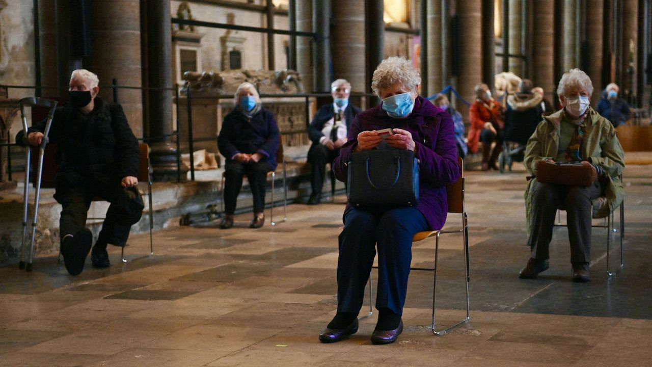 Seniorzy oczekujący w katedrze w Salisbury, po zaszczepieniu przeciwko COVID-19 (fot. PAP/EPA/N.HALL)