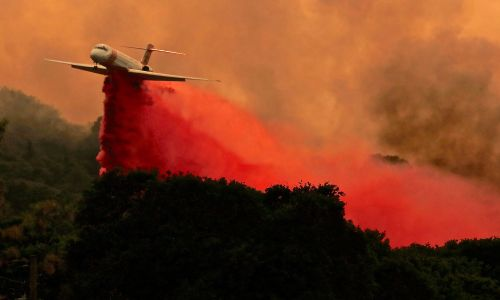 USA, 29 lipca 2018 r. Samolot przeciwpożarowy zrzuca porcję środka mającego spowolnić ogień Fire River, części wielkiego skupiska pożarow Mendocino Complex Fire w Lakeport w Kaliforni. Dwa jego ogniska – River Fire i Ranch Fire –  razem pochłonęły 22 660 hektarów, powiększając spalony teren prawie dwukrotnie od niedzieli. Ponad 10 000 osób zostało już ewakuowanych z tych terenów. Fot. PAP/EPA / ALAN SIMMONS