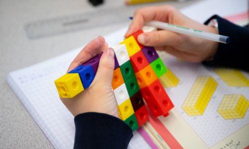 Dziecko ze szkoły podstawowej uczy się matematyki przy użyciu kolorowych kostek, 8 stycznia 2020 r. w Cardiff, Wielka Brytania. Fot. Matthew Horwood / Getty Images