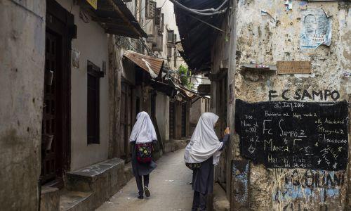 Mieszkańcy wyspy przestrzegają muzułmańskich zasad. Uczennice na ulicach Kamiennego Miasta, starej części stolicy. Fot.  Oleksandr Rupeta/NurPhoto via Getty Images