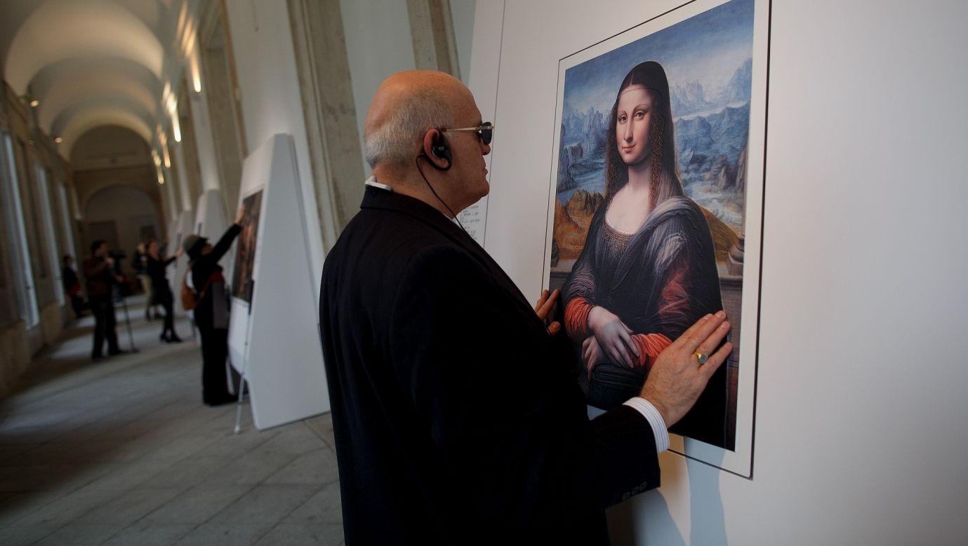 """Obrazy dla osób niedowidzących w Muzeum Prado w Madrycie. Niewidomy przechodzi od czytania tekstu w alfabecie Braille'a do kopii """"La Gioconda"""" Da Vinci, by """"zobaczyć"""" ją rękoma.  Hiszpański projekt """"Hoy toca el Prado"""" (Dotknij Prado) z 2015 roku pozwalał niewidomym lub niedowidzącym zwiedzać własnymi rękami kopie sześciu arcydzieł, powstałe przy użyciu techniki zwanej Didu, która nadaje obrazom fakturę i objętość. Fot. Pablo Blazquez Dominguez/Getty Images"""