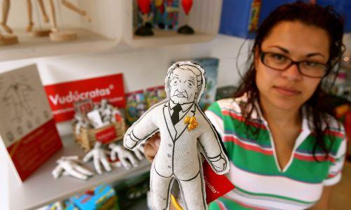 Meksykańska sprzedawczyni trzyma lalkę Andresa Manuela Lopeza Obradora, kandydata na prezydenta lewicowej Partii Rewolucji Demokratycznej (PRD). Meksykanie wtykają szpilki w laleczki w stylu voodoo przedstawiające polityków, którzy nie dotrzymują obietnic, aby nakłonić ich do stawania się lepszymi działaczami państwowymi. Meksyk 26 maja 2006 r. Fot. REUTERS / Daniel Aguilar